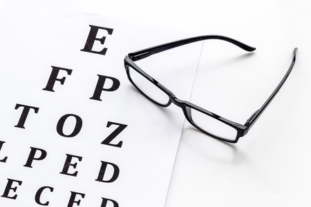 Eye examination. Eyesight test chart and glasses on white background 스톡 콘텐츠