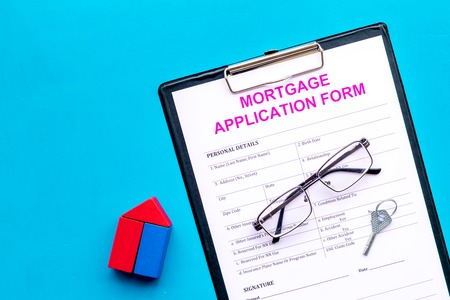 Mortgage concept. Mortgage application form near key and house made of constructor on blue background top view space for text Reklamní fotografie