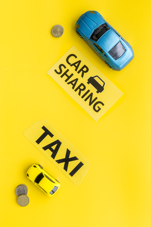 Car sharing vs taxi concept. Comparing car sharing system and taxi. Ship trip concept. Toy cars ans coins on yellow background top view copy space