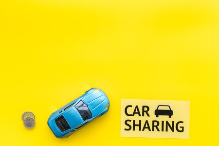 Car sharing concept, car sharing sign. Economical, chip trip. Toy car near coins on yellow background top view copy space