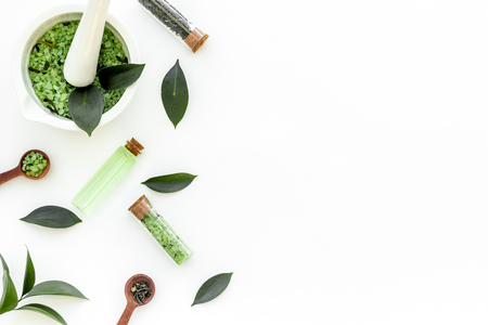 Make cosmetics with tea tree essential oil. Fresh tea tree leaves, mortar and pastel, cosmetics on white background top view border copy space