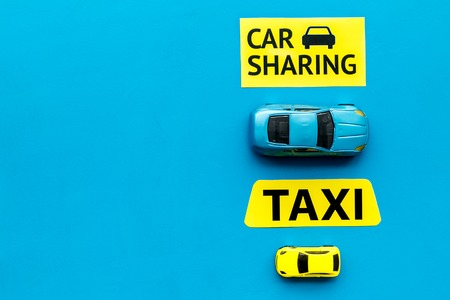 Car sharing vs taxi concept. Comparing car sharing system and taxi. Toy cars and text signs on blue background top view copy space Stock Photo