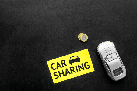 Car sharing concept, car sharing sign. Economical, chip trip. Toy car near coins on black background top view copy space