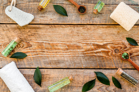 Tea tree spa composition. Fresh tea tree leaves, natural cosmetics, towel on rustic wooden background top view copy space frame Stock Photo