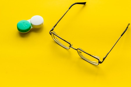 Eye problems. Glasses with transparent lenses and contact lenses on yellow background copy space