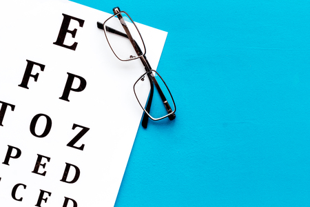 Eye examination. Eyesight test chart and glasses on blue background top view space for text Archivio Fotografico - 118162009