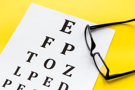 Eye examination. Eyesight test chart and glasses on yellow background Archivio Fotografico - 118161973