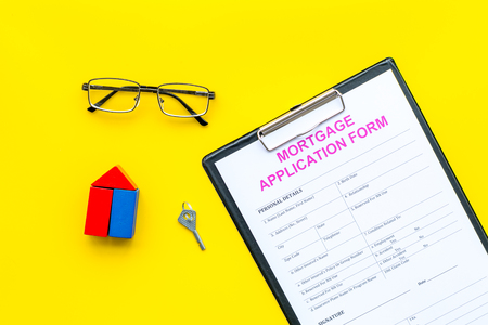 Mortgage concept. Mortgage application form near key and house made of constructor on yellow background top view