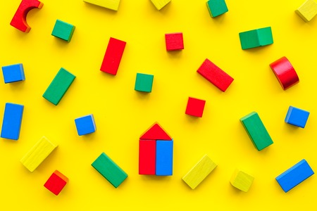 Children background. Wooden building blocks for developing and entertainment on yellow background top view
