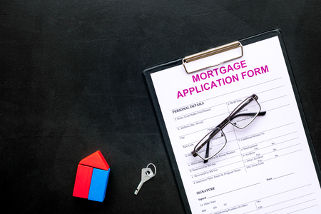 Mortgage concept. Mortgage application form near key and house made of constructor on black background top view space for text