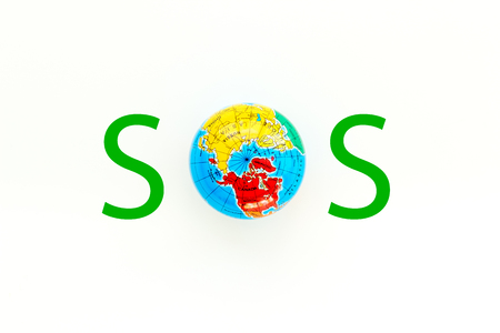 SOS Save the planet concept. The Earth as part word SOS on white background top view flat lay copy space