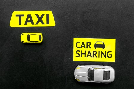 Carsharing vs taxi concept. Comparing carsharing system and taxi. Toy cars and text signs on black background top view space for text Stock Photo