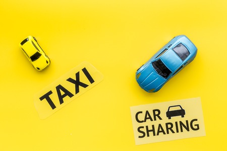 Carsharing vs taxi concept. Comparing carsharing system and taxi. Ship trip concept. Toy cars and text signs on yellow background top view copy space