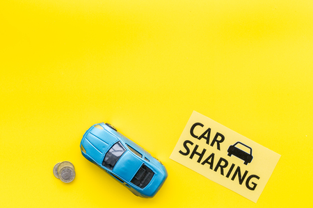 Carsharing concept, carsharing sign. Economical, chip trip. Toy car near coins on yellow background top view copy space