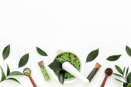 Make cosmetics with tea tree essential oil. Fresh tea tree leaves, mortar and pestel, cosmetics on white background top view border copy space