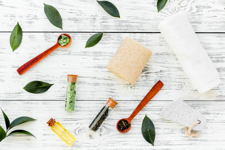 Spa composition with essential tea tree oil. Fresh tea tree leaves, natural cosmetics, towel on white wooden background top view Stock Photo