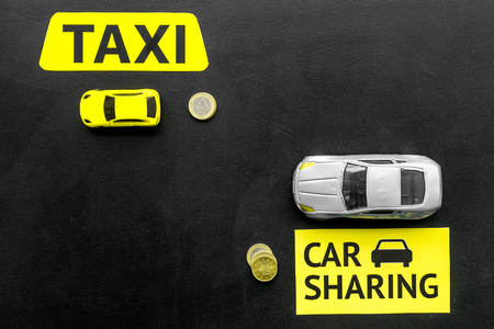 Carsharing vs taxi concept. Comparing carsharing system and taxi. Ship trip concept. Toy cars ans coins on black background top view space for text