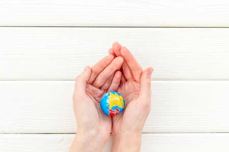SOS Save the planet concept. The earth in hands on white wooden background top view flat lay copy space