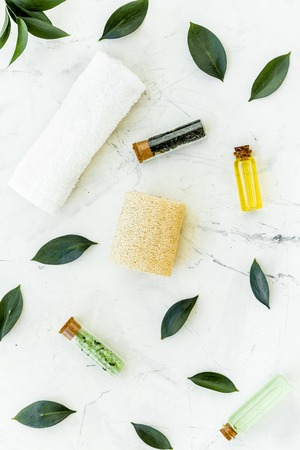 Spa composition with essential tea tree oil. Fresh tea tree leaves, natural cosmetics, towel on white stone background top view