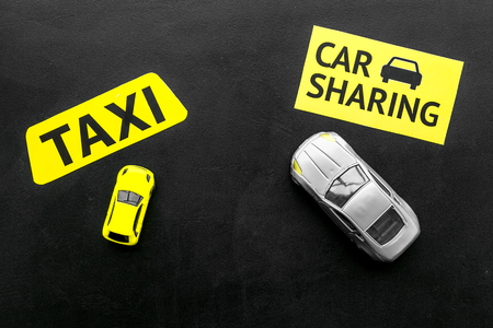 Car sharing vs taxi concept. Comparing car sharing system and taxi. Toy cars and text signs on black background top view space for text