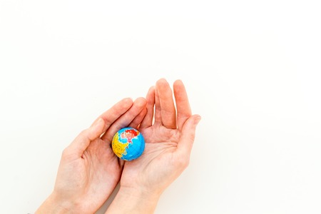 SOS Save the planet concept. The earth in hands on white background top view flat lay copy space