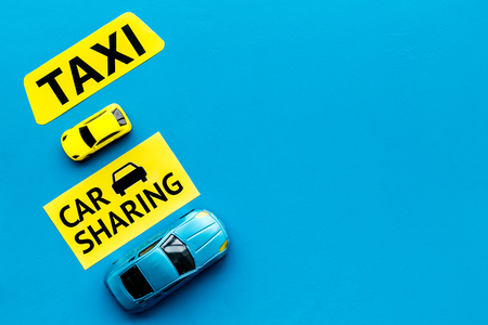 Car sharing vs taxi concept. Comparing car sharing system and taxi. Toy cars and text signs on blue background top view.