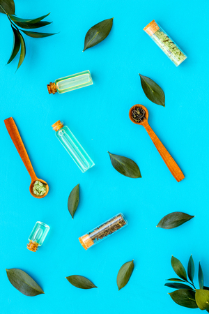 Natural organic cosmetics with tea tree essential oil near fresh tea tree leaves on blue background top view.