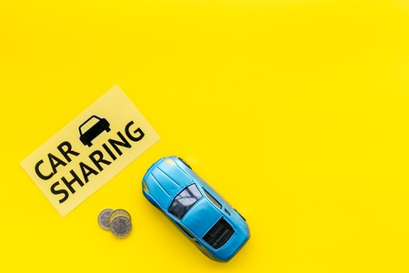 Car sharing concept, car sharing sign. Economical, chip trip. Toy car near coins on yellow background top view.