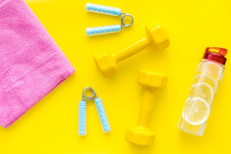 Fitness set with bars, towel, bottle of lemon water and wrist builder on yellow background top view 写真素材