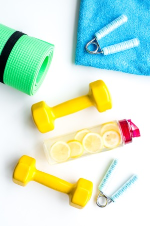 Workout with bars, mat, bottle of water and wrist builder on yellow background top view 写真素材