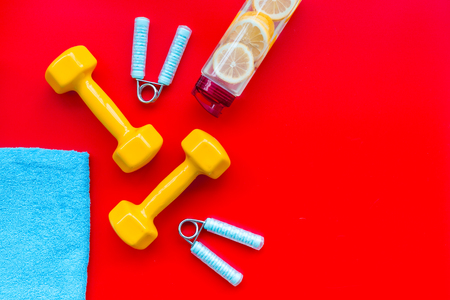 Fitness set with bars, towel, bottle of lemon water and wrist builder on red background top view mock up