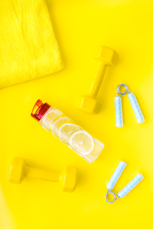 Sport with bars, towel, water and wrist builder on yellow background top view space for text.