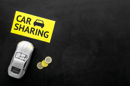Car sharing concept, car sharing sign. Economical, chip trip. Toy car near coins on black background top view.