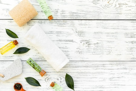 Tea tree spa composition. Fresh tea tree leaves, natural cosmetics, towel on white wooden background top view.