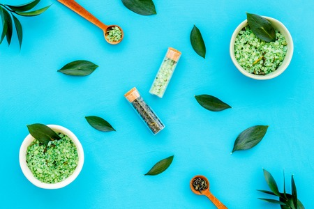 Make cosmetics with tea tree essential oil. Homemade cosmetics. Fresh tea tree leaves, mortar, cosmetics on blue background top view.