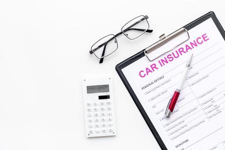 Car insurance form near glasses, calculator, pen on white background top view. Foto de archivo