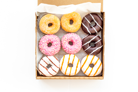 Donuts with different flavors in box on white background top view. Фото со стока
