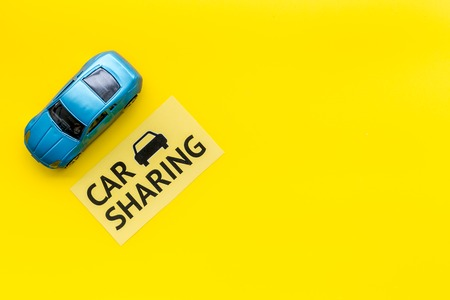 Car sharing concept. Toy car near text car sharing on yellow background top view.