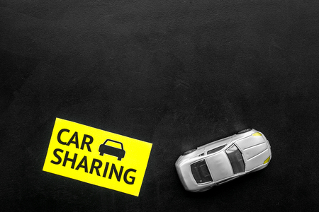Car sharing concept. Toy car near text car sharing on black background top view. Imagens - 118615556