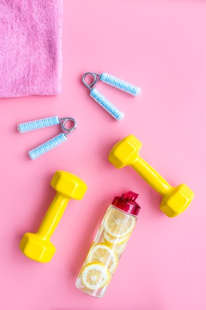 Workout with bars, towel, bottle of water and wrist builder on pink background top view