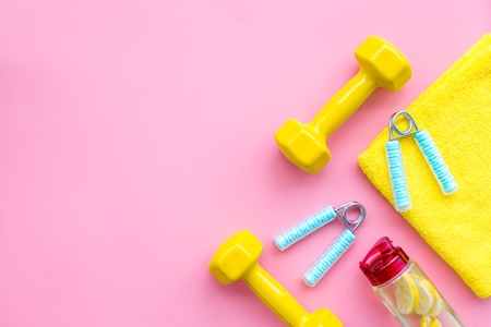 Fitness set with bars, towel, bottle of lemon water and wrist builder on pink background top view mock up