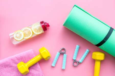 Fitness set with bars, towel, bottle of lemon water and wrist builder on pink background top view