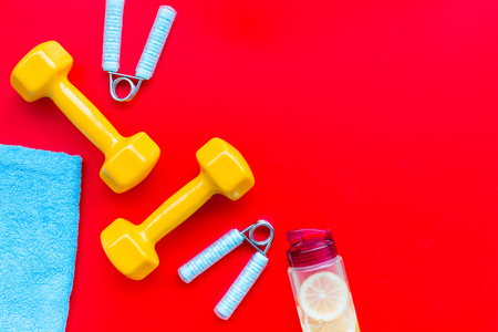 Fitness background with sport equipment for gym and home workout on red background top view copyspace