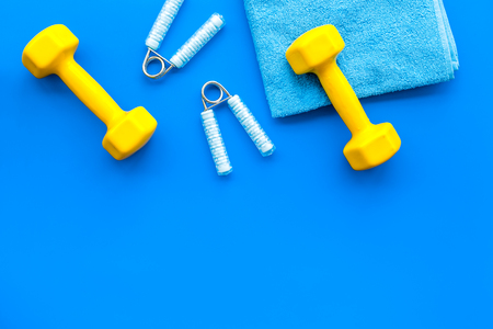 Fitness set with bars, towel and wrist builder on blue background top view mock up.