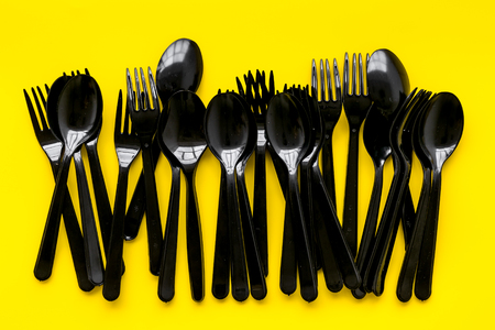 Ecology. Plastic spoons and forks utilization and the Earth protection concept with flatware on yellow background top view
