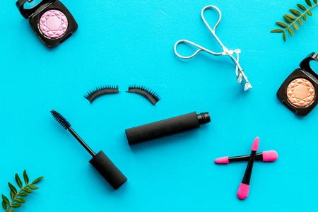 Make up set with woman organic decorative cosmetic with eye shadows and mascara on blue background top view