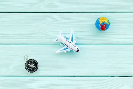 SOS Save the planet and eco concept with the earth, plane and compass on blue wooden background flat lay mockup