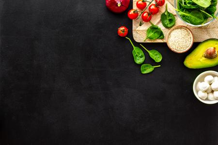 Ingredients for fresh vegetable salad on black kitchen desk top view.