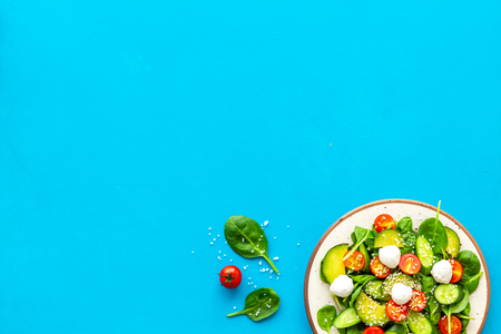 Healthy lunch. Fresh vegetable salad on blue background top view.