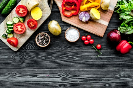 Fresh food with raw vegetable ingredients for vegetarian kitchen on black wooden background top view mock-up Stock Photo